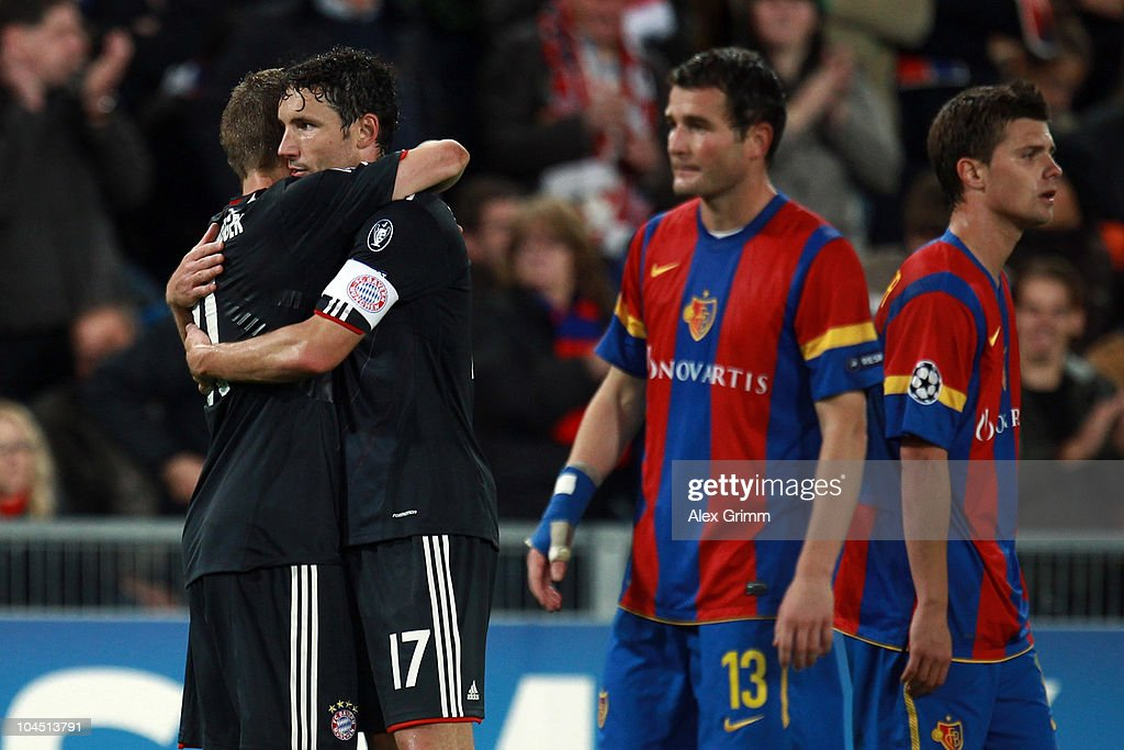 Mark van Bommel (2L) of Muenchen hugs <a gi-track='captionPersonalityLinkClicked' href=/galleries/search?phrase=Bastian+Schweinsteiger&family=editorial&specificpeople=203122 ng-click='$event.stopPropagation()'>Bastian Schweinsteiger</a> as <a gi-track='captionPersonalityLinkClicked' href=/galleries/search?phrase=Alexander+Frei&family=editorial&specificpeople=534543 ng-click='$event.stopPropagation()'>Alexander Frei</a> (2R) and <a gi-track='captionPersonalityLinkClicked' href=/galleries/search?phrase=Valentin+Stocker&family=editorial&specificpeople=5522265 ng-click='$event.stopPropagation()'>Valentin Stocker</a> of Basel react during the UEFA Champions League group E match between FC Basel and FC Bayern Muenchen at the St. Jakob Park stadium on September 28, 2010 in Basel, Switzerland.