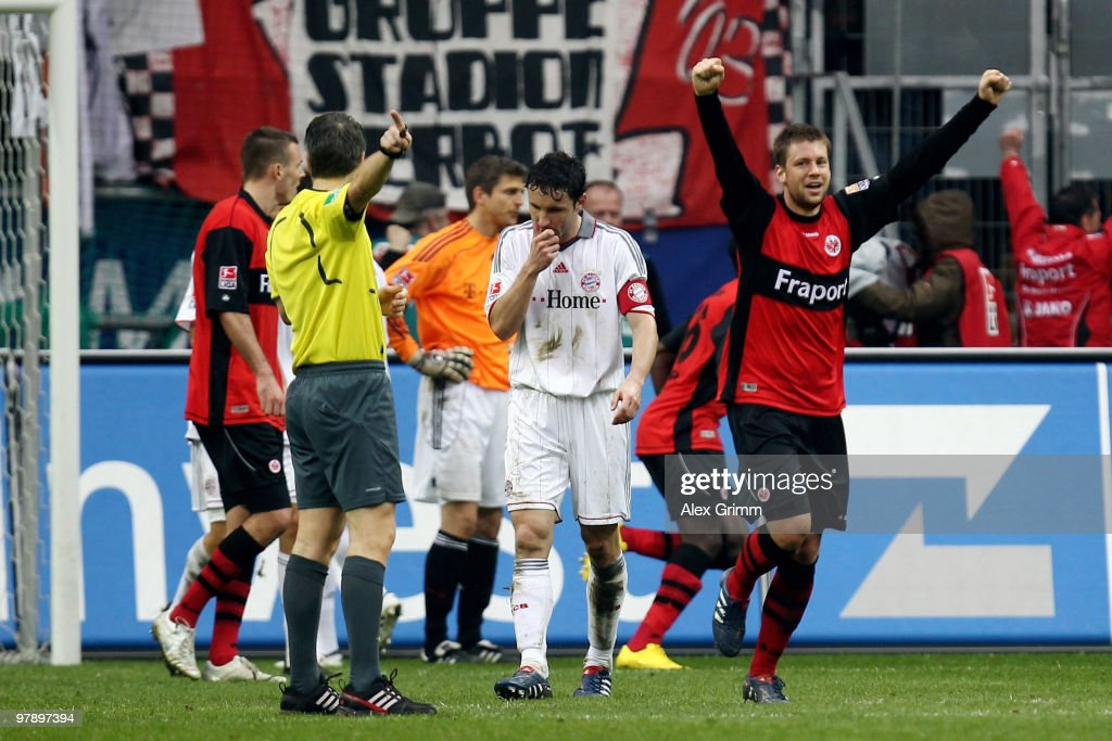 Mark van Bommel (C) of Muenchen reacts as Marco Russ (R) of Frankfurt celebrates during the Bundesliga match between Eintracht Frankfurt and Bayern Muenchen at the Commerzbank Arena on March 20, 2010 in Frankfurt, Germany.