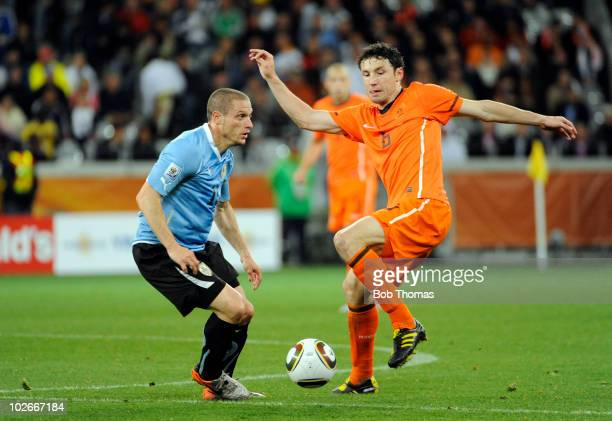 Mark van Bommel of the Netherlands handles the ball against Diego Perez of Uruguay during the 2010 FIFA World Cup South Africa Semi Final match...