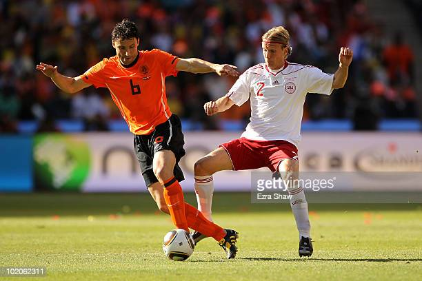 Mark Van Bommel of the Netherlands is challenged by Christian Poulsen of Denmark during the 2010 FIFA World Cup Group E match between Netherlands and...