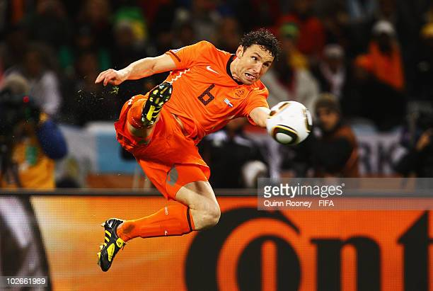 Mark Van Bommel of the Netherlands jumps for the ball during the 2010 FIFA World Cup South Africa Semi Final match between Uruguay and the...