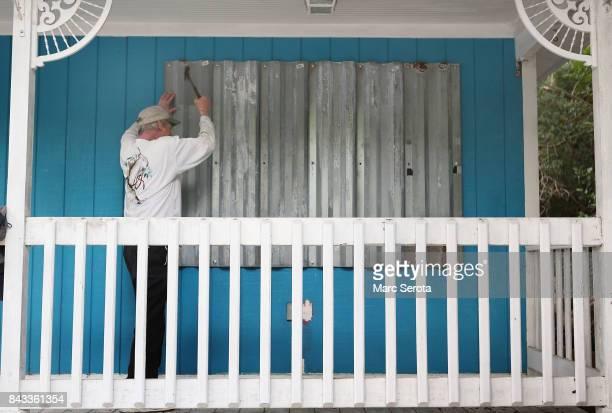 Mark Waddell installs hurricane shutters to a house in the Florida Keys on September 6 2017 in Islamorada Florida Hurricane Irma has grown to a...