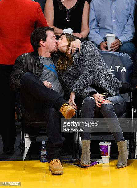 Mark Wahlberg kisses his wife Rhea Durham at a basketball game between the Milwaukee Bucks and the Los Angeles Lakers at Staples Center on February...
