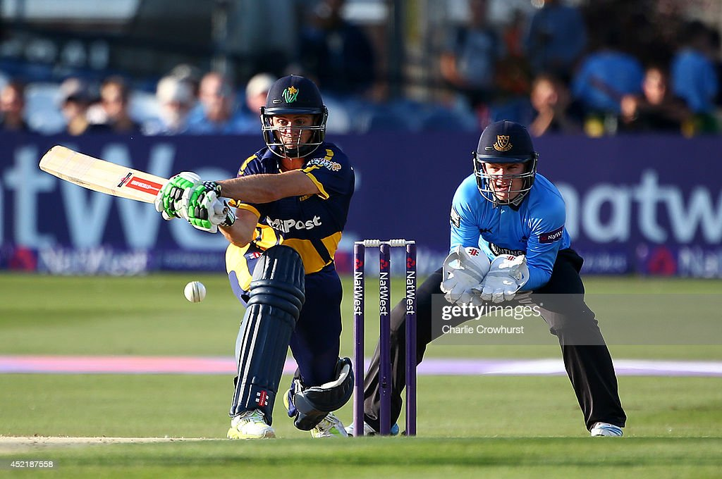 Mark Wallace of Glamorgan looks to play a sweep shot while Ben Brown of Sussex looks on during the Natwest T20 Blast match between Sussex Sharks and Glamorgan at The BrightonAndHoveJobs.com County Ground on July 15, 2014 in Hove, England.