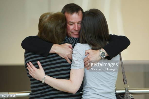 Mark Wardle from Gloucester gives his wife Sheila and daughter Gemma a hug as he arrives at Heathrow Terminal 5 after being delayed in Jakarta since...