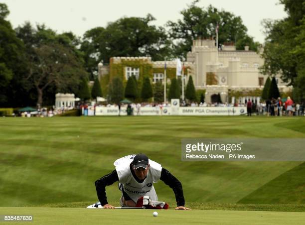 Mark Warren's caddie looks at his putt on the 1st green during Round 3 of the BMW PGA Championship at Wentworth Golf Club Surrey