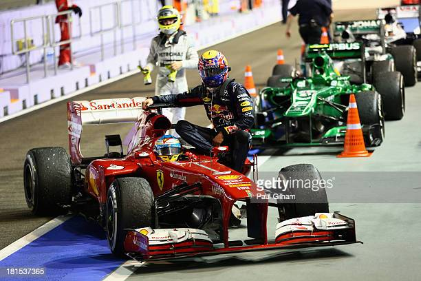 Mark Webber of Australia and Infiniti Red Bull racing is given a lift back to pits by Fernando Alonso of Spain and Ferrari after his engine blew up...