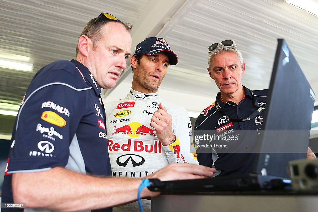 Mark Webber of Australia and Infiniti Red Bull Racing looks at a laptop with his mechanics during the Top Gear Festival at Sydney Motorsport Park on March 9, 2013 in Sydney, Australia.