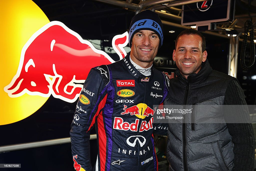 Mark Webber of Australia and Infiniti Red Bull Racing meets with Spanish golfer Sergio Garcia in his team garage during day one of Formula One winter...