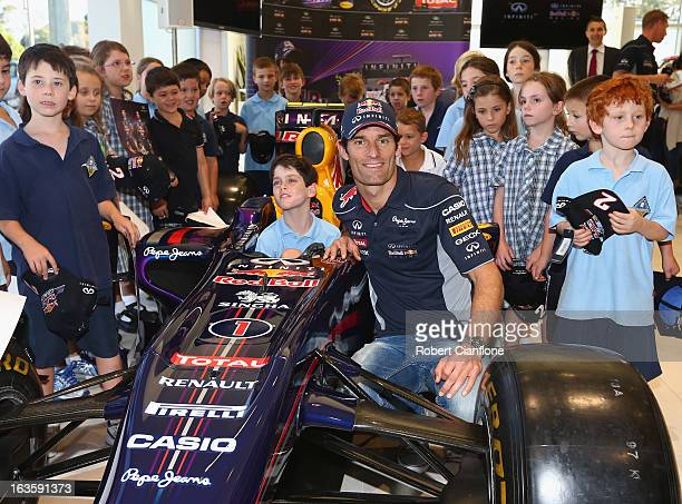 Mark Webber of Australia and Infiniti Red Bull Racing poses with school children from Brighton Primary School at the Infiniti dealership on March 13...