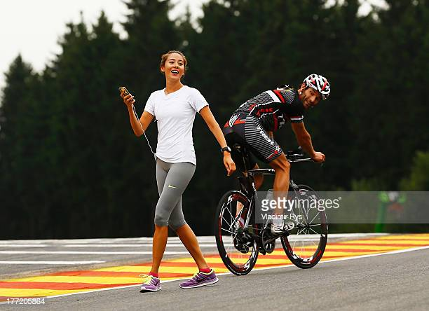 Mark Webber of Australia and Infiniti Red Bull Racing rides his bike past Jenson Buttons girlfriend Jessica Michibata as he rounds the circuit during...