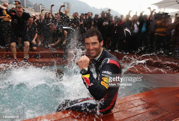 Mark Webber of Australia and Red Bull Racing celebrates winning the race by jumping into the swimming pool on the Red Bull Energy Station following...