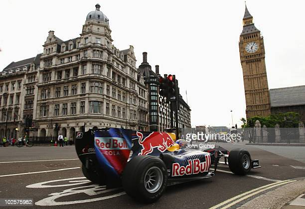 Mark Webber of Australia and Red Bull Racing drives round Parliament Square and completes a pit stop in front of the Houses of Parliament on July 2...
