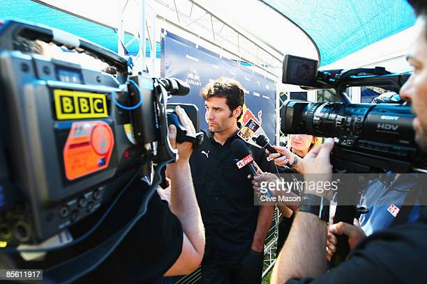 Mark Webber of Australia and Red Bull Racing is interviewed by the media in the paddock during previews to the Australian Formula One Grand Prix at...