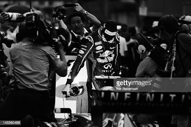 Mark Webber of Australia and Red Bull Racing pours champagne onto his car as he celebrates winning the Monaco Formula One Grand Prix at the Circuit...