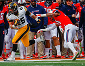Mark Weisman of the Iowa Hawkeyes runs the ball and is pushed out of bounds by Zane Petty of the Illinois Fighting Illini at Memorial Stadium on...