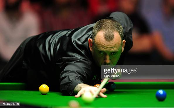 Mark Williams of Wales plays a shot during his first round match against Ronnie O'Sullivan of England during Day Three of The Dafabet Masters at...
