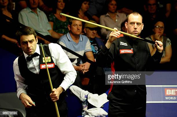 Mark Williams of Wales shows his disappointment as Ronnie O'Sullivan of England avoids his cue during the Betfredcom World Snooker Championships at...