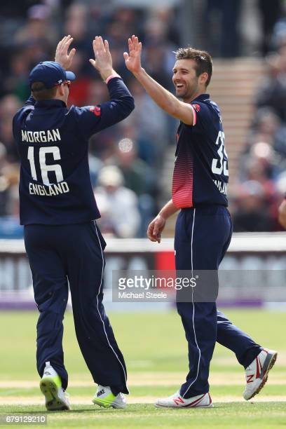 Mark Wood celebrates with Eoin Morgan after taking the wicket of Paul Stirling of Ireland during the Royal London One Day International match between...