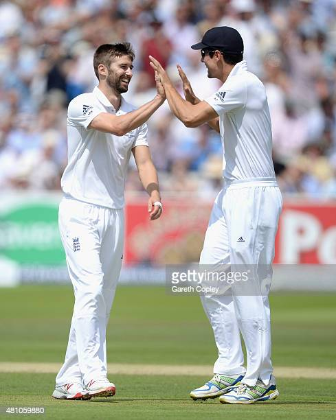 Mark Wood of England celebrates with captain Alastair Cook after dismissing Australian captain Michael Clarke during day two of the 2nd Investec...