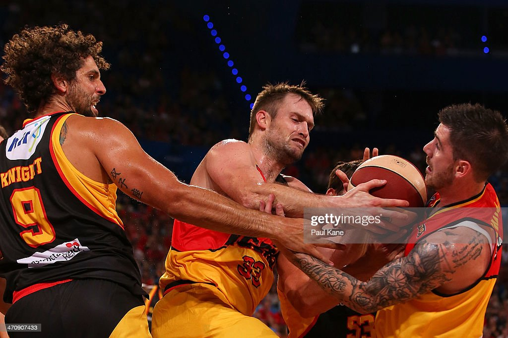 Mark Worthington and Nate Tomlinson of the Tigers contest for a rebound against Matt Knight of the Wildcats during the round 19 NBL match between the Perth Wildcats and the Melbourne Tigers at Perth Arena on February 21, 2014 in Perth, Australia.