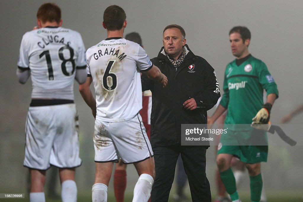 Mark Yates (2R) manager of Cheltenham Town shakes hands with Luke Graham (2L) of Hereford United after his sides 2-1 extra time victory during the FA Cup with Budweiser Second Round Replay match between Hereford United and Cheltenham Town at Edgar Street Athletic Ground on December 11, 2012 in Hereford, England.