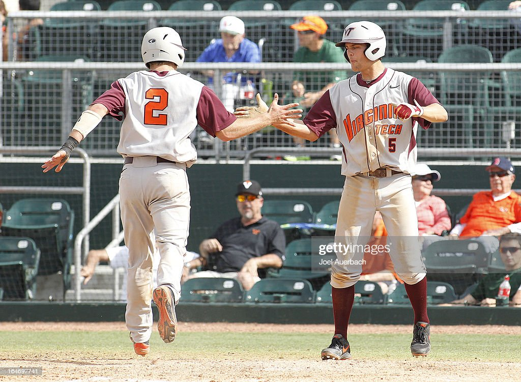 Mark Zagunis #2 and Chad Pinder #5 of the Virginia Tech Hokies celebrate after scoring two runs against the Miami Hurricanes in the tenth inning on March 24, 2013 at Alex Rodriguez Park at Mark Light Field in Coral Gables, Florida. Virginia Tech defeated Miami 8-5 in 10 innings.