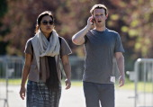 Mark Zuckerberg chief executive officer and founder of Facebook Inc right talks on the phone while arriving for a morning session his wife Priscilla...