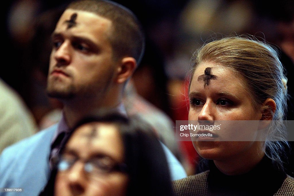 Marked with a cross of black ash on the forehead, Catholics pray during an Ash Wednesday Mass at the Cathedral of St. Matthew the Apostle February 22, 2012 in Washington, DC. Ash Wednesday begins the season of Lent, the 40-day penitential period before Easter when Christians celebrate Christ's resurrection from the dead. One of seven Ash Wednesday services at the cathedral, the noontime mass was packed with worshippers, leaving many to stand in the back and the aisles of St. Matthew.