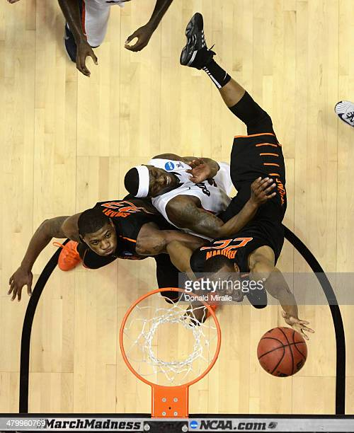 Markel Brown and Marcus Smart of the Oklahoma State Cowboys go for the ball against Gary Bell Jr #5 of the Gonzaga Bulldogs during the second round...