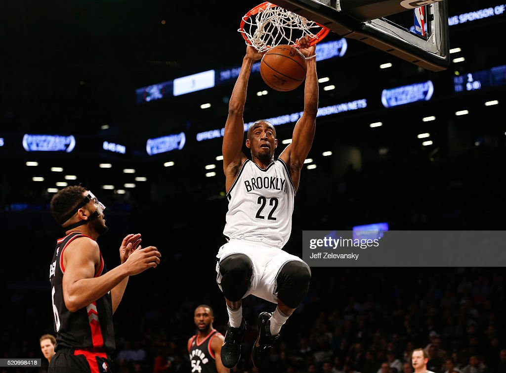 Markel Brown #22 of the Brooklyn Nets dunks in front of Cory Joseph #6 of the Toronto Raptors during their game at the Barclays Center on April 13, 2016 in New York City.