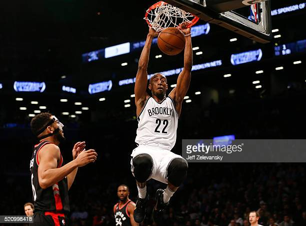 Markel Brown of the Brooklyn Nets dunks in front of Cory Joseph of the Toronto Raptors during their game at the Barclays Center on April 13 2016 in...