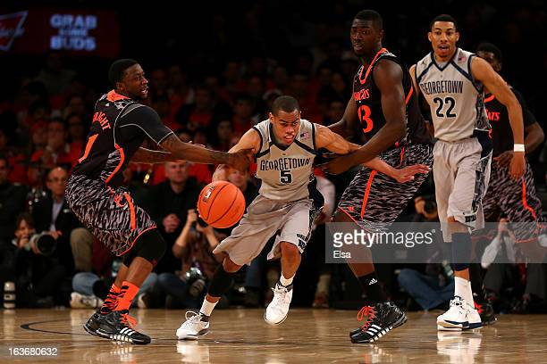 Markel Starks of the Georgetown Hoyas attempts to drive the ball as he is defended by Cashmere Wright and Cheikh Mbodj of the Cincinnati Bearcats in...