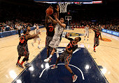 Markel Starks of the Georgetown Hoyas drives for a shot attempt against Cheikh Mbodj and Titus Rubles of the Cincinnati Bearcats during the...
