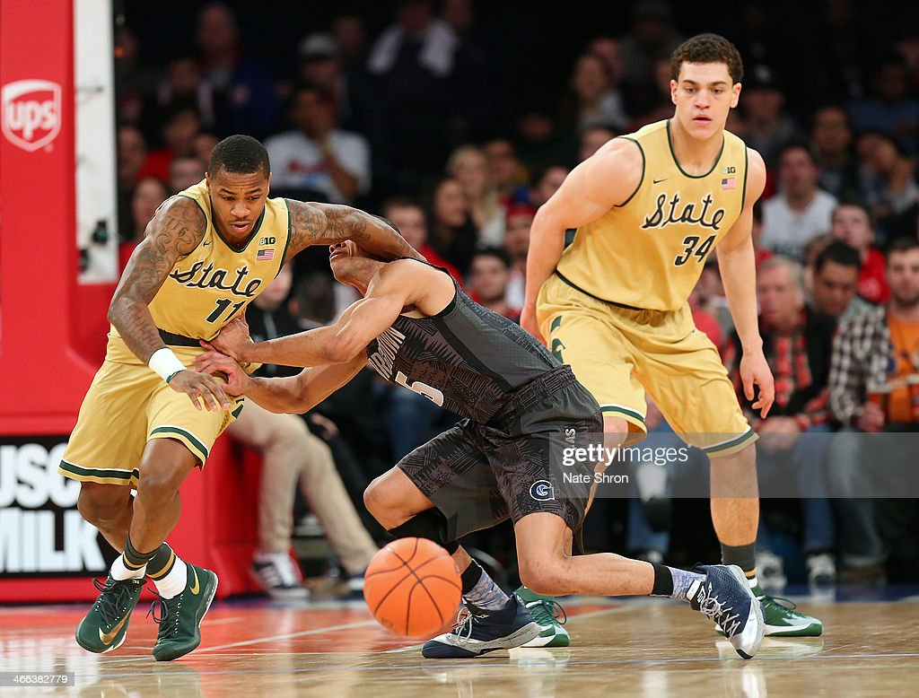 Markel Starks of the Georgetown Hoyas reaches for the ball against Keith Appling and Gavin Schilling of the Michigan State Spartans during the game...