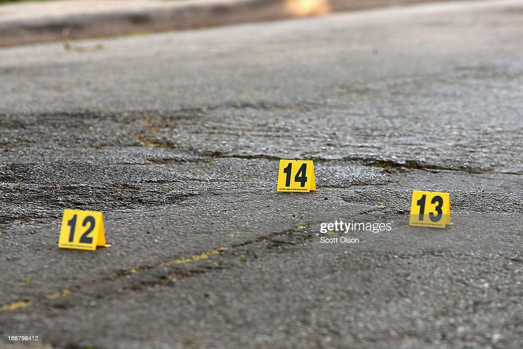 Markers placed by Chicago police protect for evidence shell casings that dropped in the street near the location where two men were shot and wounded in the South Shore neighborhood on May 14, 2013 in Chicago, Illinois. The shooting was the first of several that left two men dead and 11 others wounded in the city between Monday afternoon and the early hours of Tuesday morning.