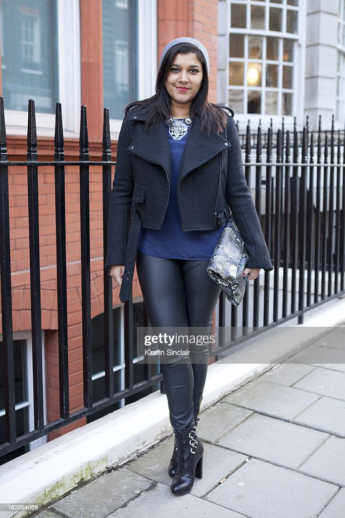 Market Editor for ELLE Magazine Bonnie Rakhit wears H&M hat, Christopher Kane jacket, vintage snake skin clutch, Christian Louboutin shoes, Banana Republic top and Oasis Jewellery on day 3 of London Womens Fashion Week Autumn/Winter 2013 on February 17, 2013 in London, England.