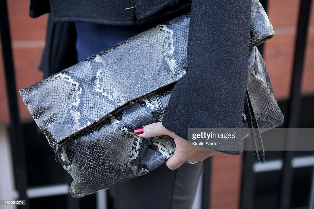 Market Editor for ELLE Magazine carries a vintage snake skin clutch on day 3 of London Womens Fashion Week Autumn/Winter 2013 on February 17, 2013 in London, England.