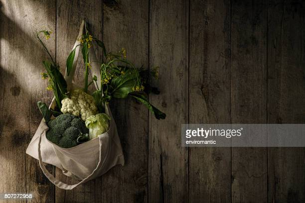 Market fresh green leafy vegetables in a cotton reusable shopping bag hanging from an old hook on an old weathered wooden panel wall.