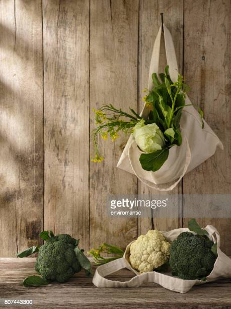 Market fresh green leafy vegetables in a cotton reusable shopping bag hanging from an old hook on an old weathered wooden panel wall, with more vegetables under the bag on a wooden table.