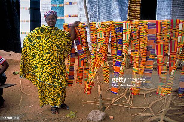 Market lady displaying kente cloth for sale along the roadside in Bonwire near Kumasi the capitol of the Ashanti Region in Ghana West Africa