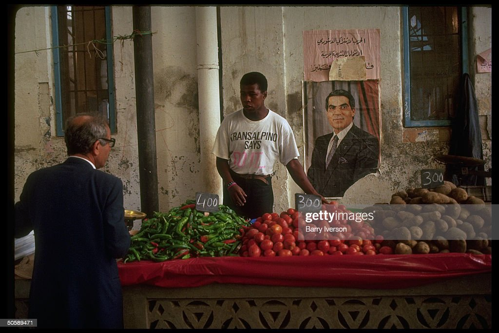 Market merchant answering customer's query, manning peppers, tomatoes & potatoes-heaped stand by wall w. portrait of Pres. Ben Ali.