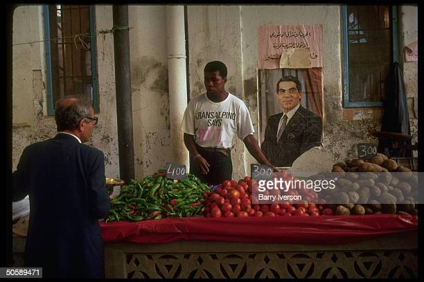 Market merchant answering customer's query manning peppers tomatoes potatoesheaped stand by wall w portrait of Pres Ben Ali