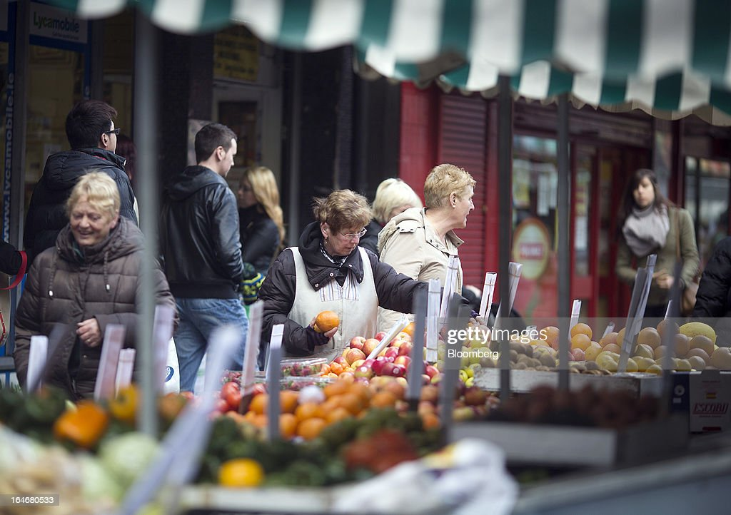 A market trader arranges her fruit and vegetable display on a stall in Moore Street in Dublin, Ireland, on Saturday, March 16, 2013. Ireland's renewed competiveness makes it a beacon for the U.S. companies such as EBay, Google Inc. and Facebook Inc., which have expanded their operations in the country over the past two years. Photographer: Simon Dawson/Bloomberg via Getty Images