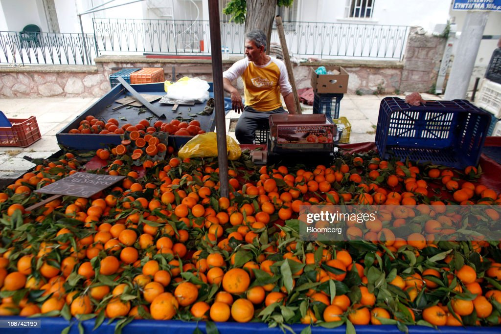 A market trader sits behind his orange stall at an open air market in the Ilioupolis district of Athens, Greece, on Tuesday, May 14, 2013. Greek Prime Minister Antonis Samaras said the country can beat the targets set under its 240 billion-euro ($311 billion) International Monetary Fund and euro area bailout program and return to bond markets in the first half of next year. Photographer: Kostas Tsironis/Bloomberg via Getty Images
