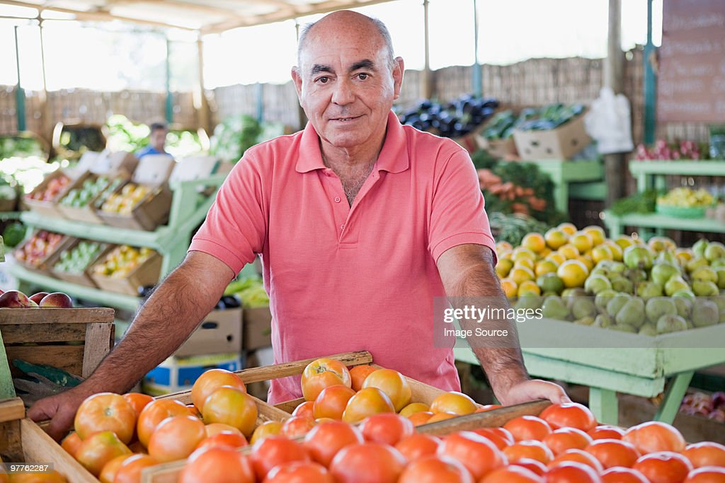 Market trader with tomatoes