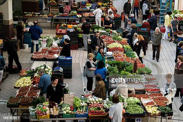 Market traders sell fresh fruit and vegetables from stalls inside Lehel Piac market in Budapest Hungary on Wednesday May 15 2013 Hungary's economy...