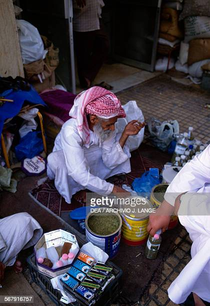 Market vendor on a rug selling water and different products Al Ain United Arab Emirates