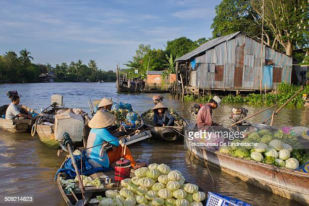 Market vendors wearing traditional asian conical bamboo hats selling vegetables and fruit from small boats early in the morning at the authentic...