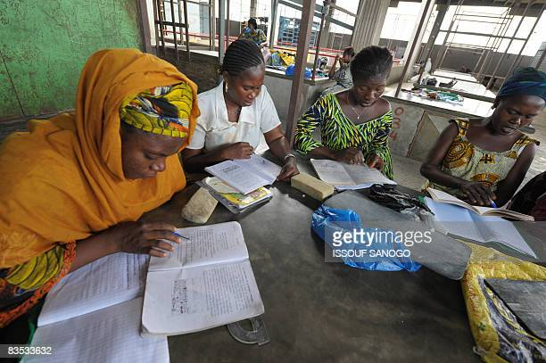 KOFFI Market workers attend a class on October 28 2008 in the market of a popular quarter of Abidjan where stall holders have put aside their tasks...
